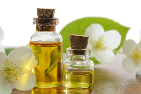Aroma oil bottles arranged with jasmine flowers and petals