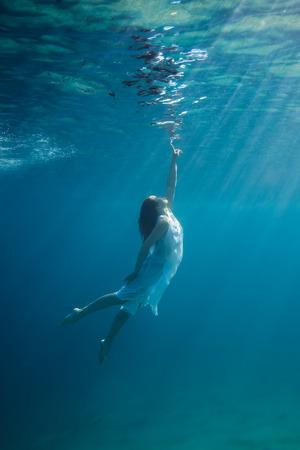 pelirrojas: Joven mujer pelirroja bajo el agua en un mar