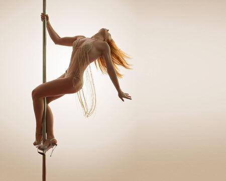 pole dancing: Jeune femme rousse au pole dancing