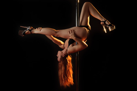 pole dancer: Young redhead woman hanging on a pole