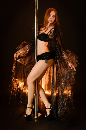 poledance: Young redhead woman standing at the pole Stock Photo