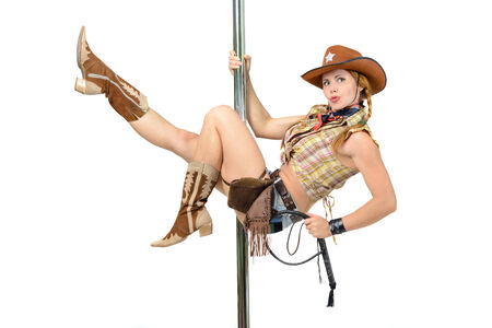 white pole: Young woman in cowboy suite hanging on a pole Stock Photo