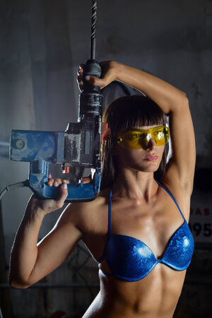 Young sporty woman in swimsuit working with heavy tools 写真素材
