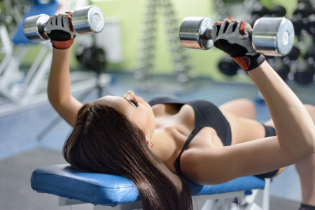 only the biceps: Young woman training in a gym with dumbbells Stock Photo
