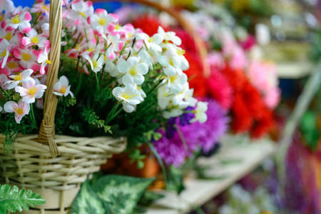 artifical: Colorful artifical flowers in abasket on a shelf