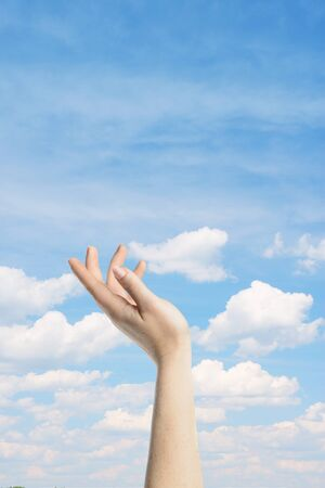 hand reaching: Elegant womans hand reaching blue peaceful sky
