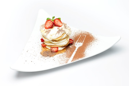 chocolate powder: Sweet dessert with cut strawberries and cream, on a plate decorated with chocolate powder
