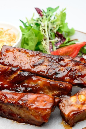 Fried pork ribs on a wooden plate decorated with salad 写真素材