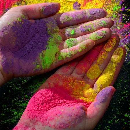 Womans hands covered with bright dry holi paint 写真素材