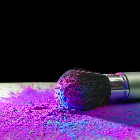 dry powder: Makeup brush covered with bright holi dry powder paint Stock Photo