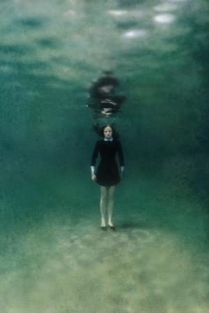수중 모래에 검은 드레스 서에서 젊은 여자 스톡 콘텐츠