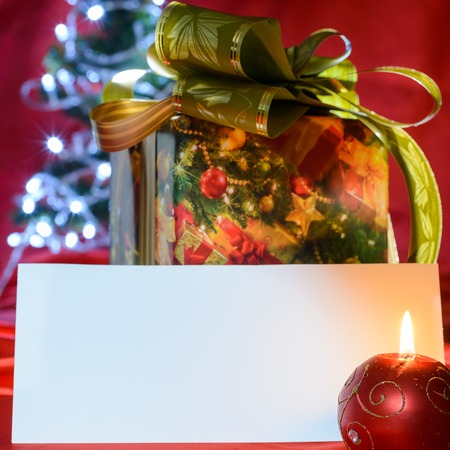 new year eve beads: Blank paper on Christmas gift background lighted by candle
