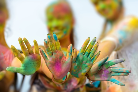 Holi painted hands of three defocused girls