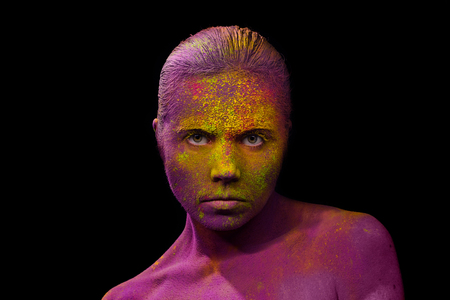 alien face: Young cheerful woman fully covered with holi paint powder Stock Photo