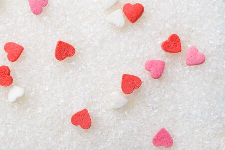 Heart shaped small candies on sugar as background