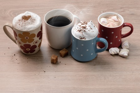 Cups of different kinds of coffee drinks as family or friendly company symbol. Everybody finds his own kind of coffee. Reklamní fotografie