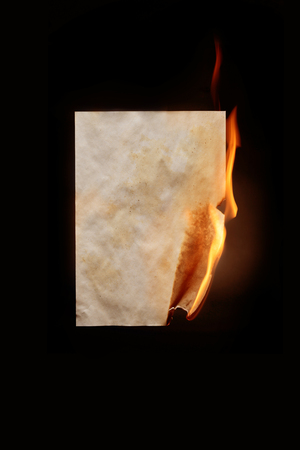 Burning sheet of paper on dark background