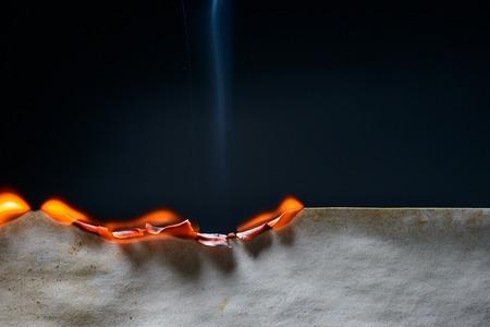 Burning edge of paper on dark background