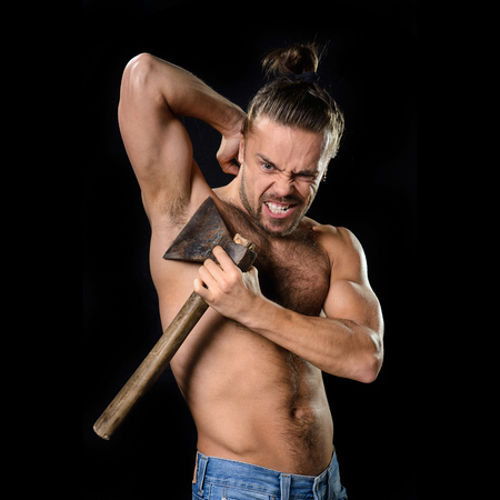 hairy: Brutal young man shaving himself with rusty dull axe Stock Photo