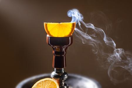 lounge: Smoking hookah with fruit head on dark background Stock Photo