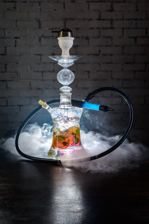 Colorful glass smoking hookah with fruits inside