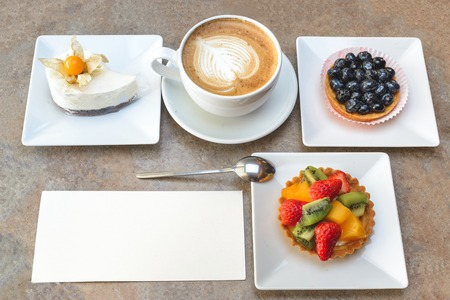 phisalis: Different fruit cakes and cup of capuccino with blank card on table Stock Photo