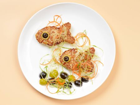 fish plate: Funny fish cutlets on white plate decorated with olives and salad