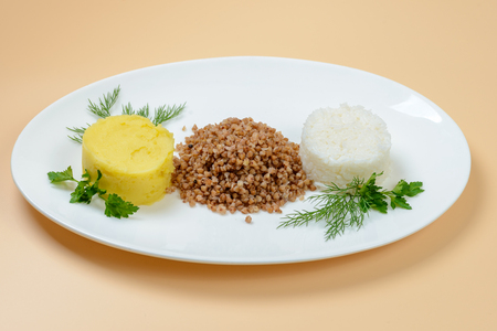 buckwheat, potatoes, rice garnish on white oval late