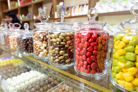 Candies in glass jars in candy shop