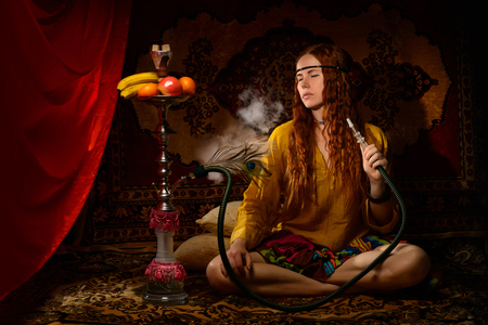 Young woman dressed in hippie style smoking hookah Reklamní fotografie