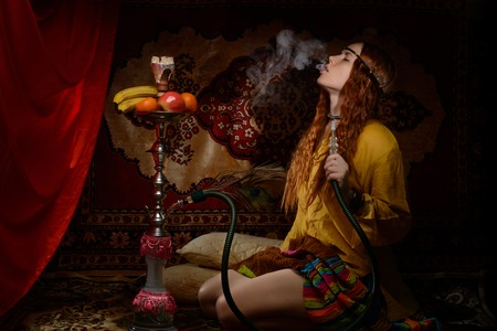 Young woman dressed in hippie style smoking hookah 写真素材