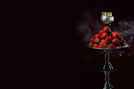 Smoking hookah with fruit head on dark background 写真素材