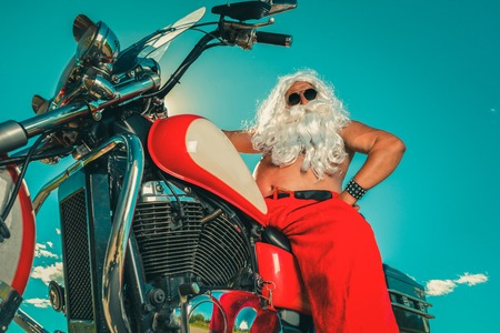 old biker: Sunburned Santa biker riding motorcycle on summer vacations Stock Photo