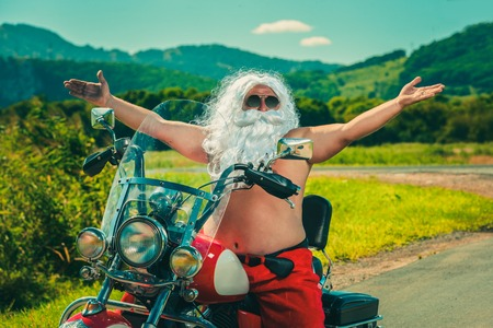 Sunburned Santa biker riding motorcycle on summer vacations Stock Photo