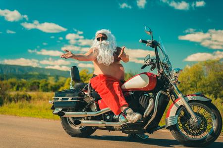 Sunburned Santa biker riding motorcycle on summer vacations Stock Photo
