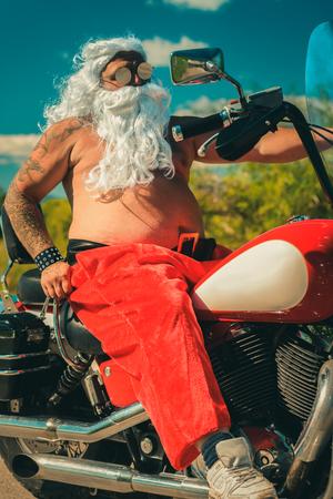 sunburned: Sunburned Santa biker riding motorcycle on summer vacations Stock Photo