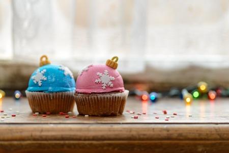 windowsill: Two Christmas decorated cupcakes on wooden windowsill