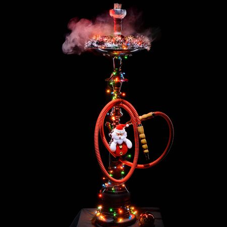 smoking pipe: Smoking hookah with New Years decorations on dark background