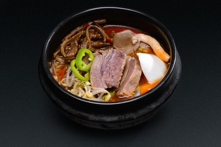 Korean soup with meat and mushrooms in black dish