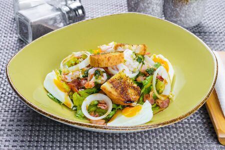 Korean salad with egg and seafood in green dish