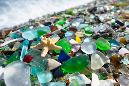 Beach fully covered with multicolored glass pebble. Wonder of nature.