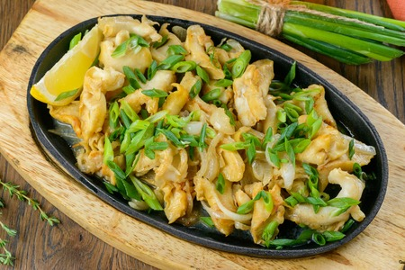 Fried clamps with greens on oval fry pan garnished with herbs