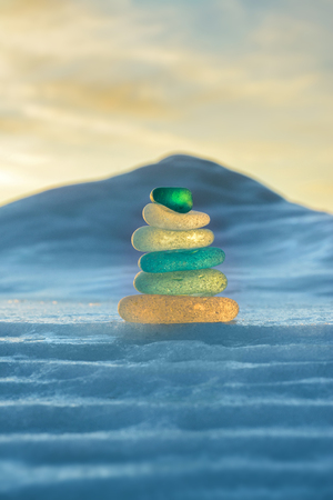 Stack of glass pebble on sunset