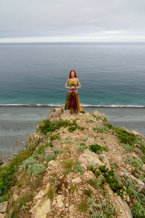 Long-haired girl walking on sea shore in springtime