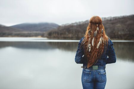 Long-haired girl on lake shore in autumn season