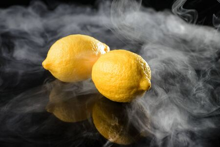 Fragrant lemon smoke on black mirrored background Imagens