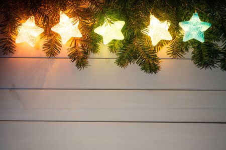 Light wooden background with glow Christmas decorations Stock Photo