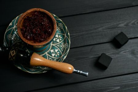 Parts of antique hookah in dark on black wooden background Stock Photo