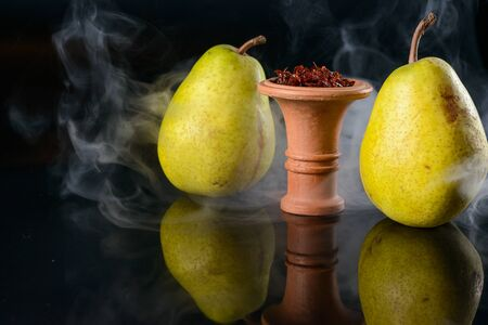 Fragrant pear tobacco for hookah in bowl on black glass background Stock Photo