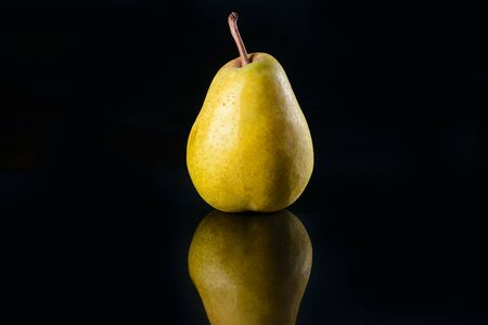 Whole fragrant pear on glass black background